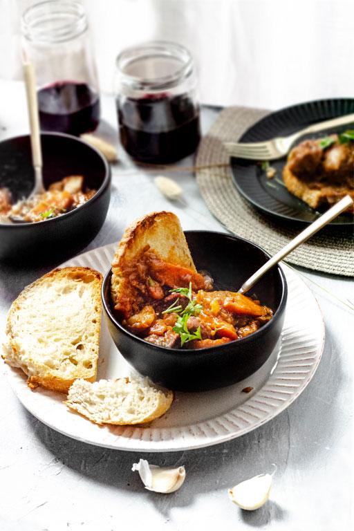 "vegan seitan ""beef"" bourguignon served in dishes"