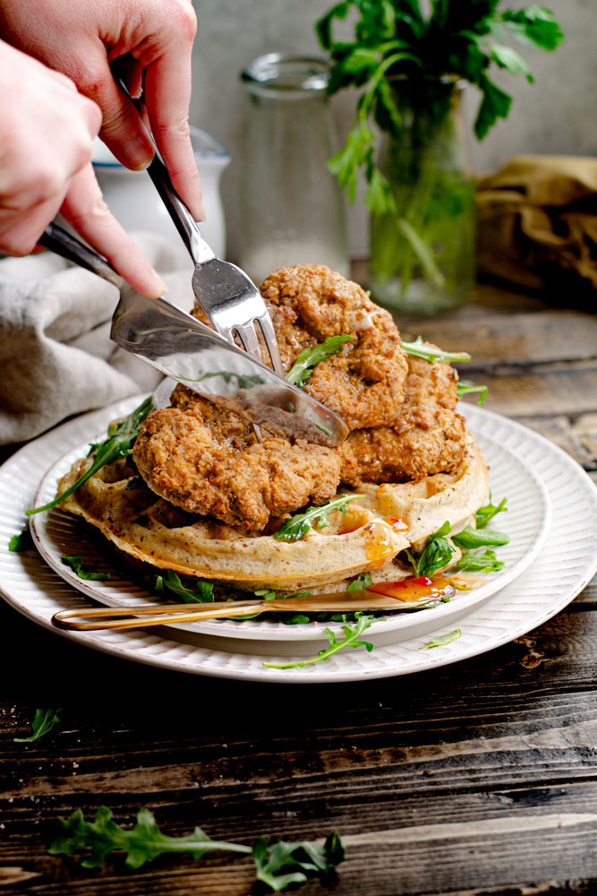 cutting into the chicken and waffles