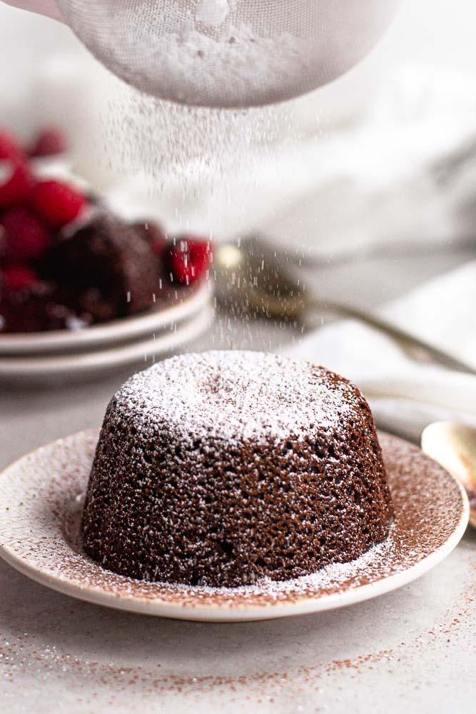 sprinkling powdered sugar on the cakes