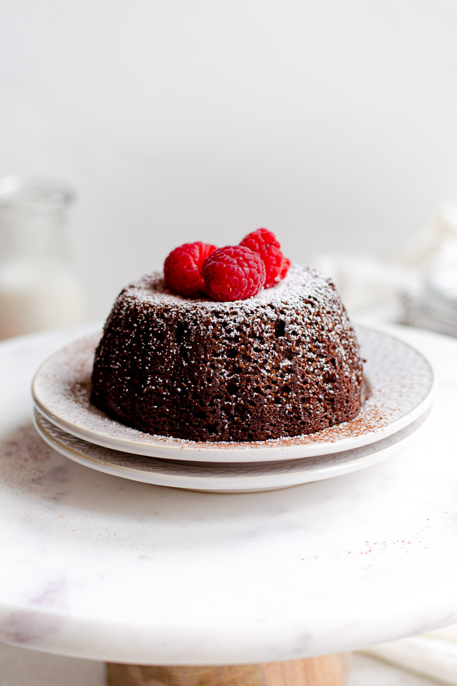 vegan chocolate cake on plate with raspberries