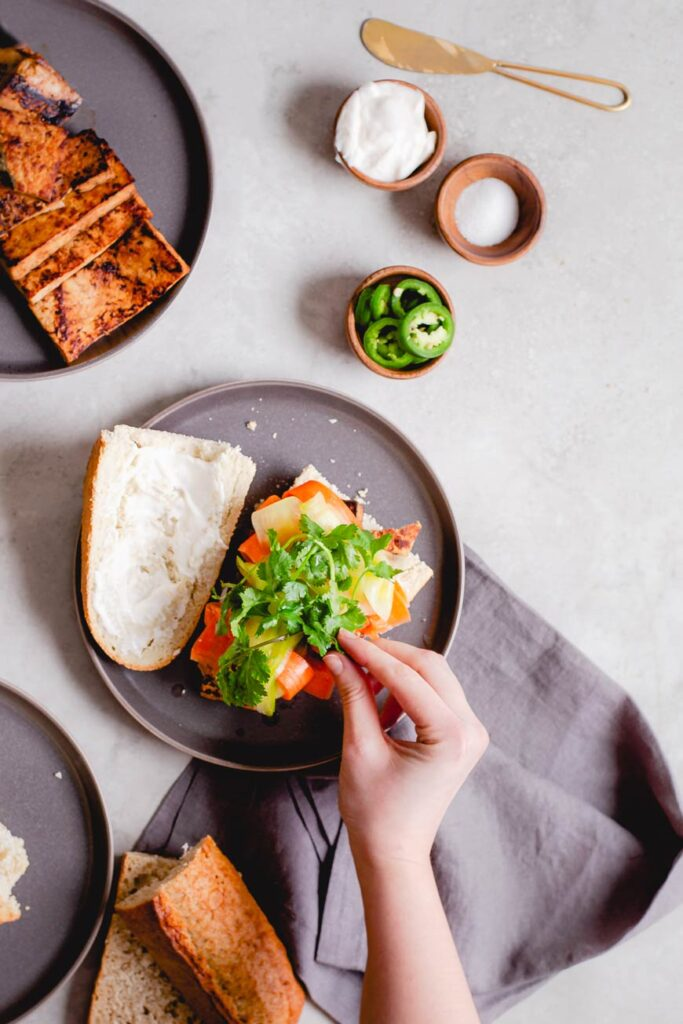 layering on ingredients on the vegan sandwich