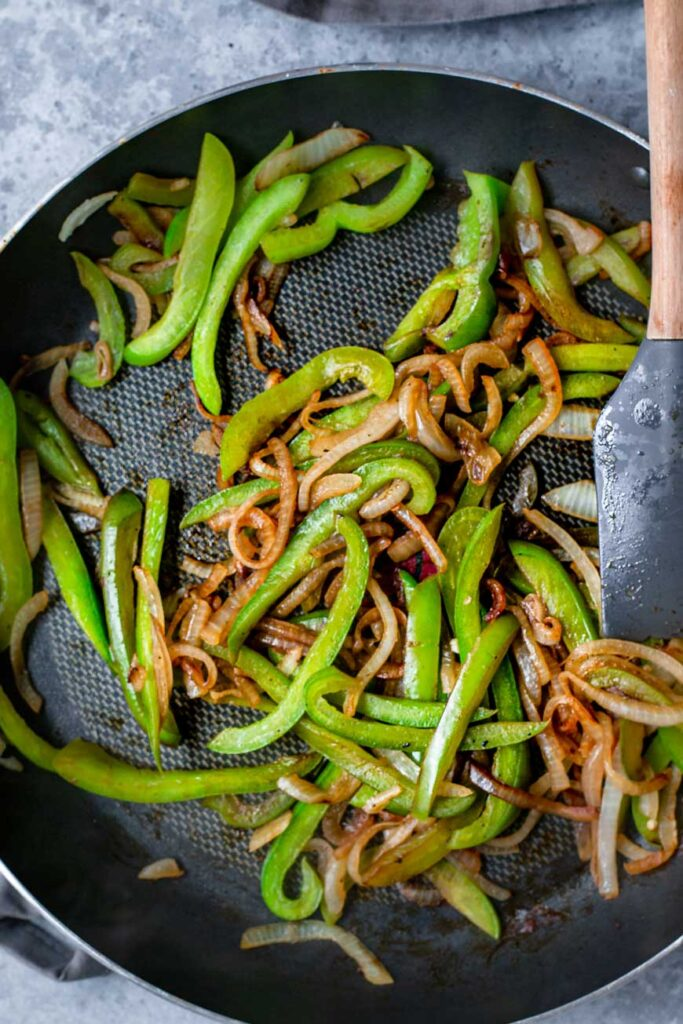 sautéed green bell peppers and onions in pan