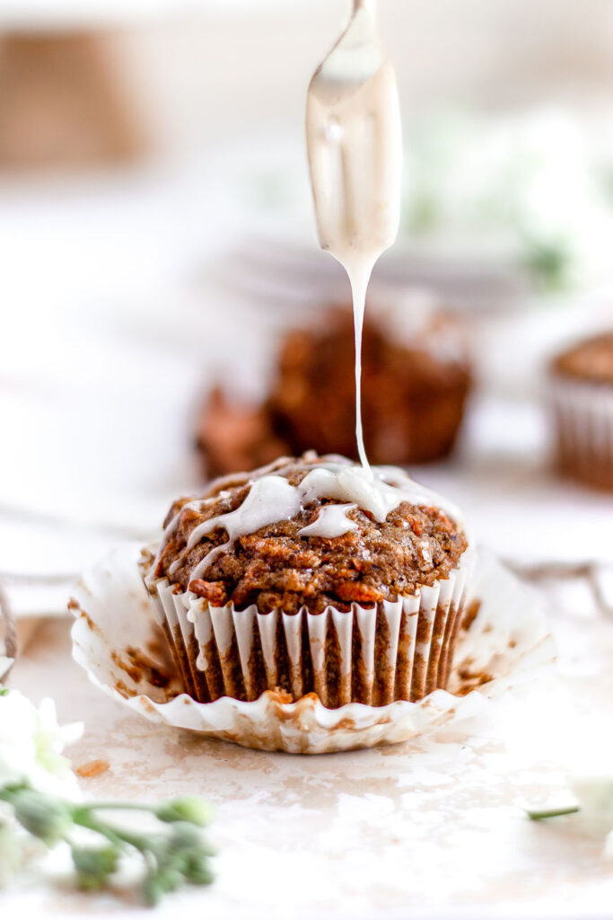 drizzling dairy-free cream cheese glaze on carrot muffin