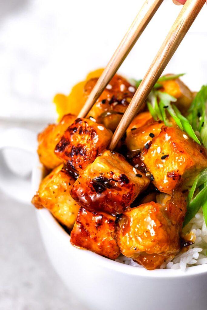 crispy orange tofu in chopsticks
