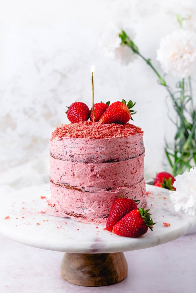 easy strawberry crunch cake on a cake stand with a candle